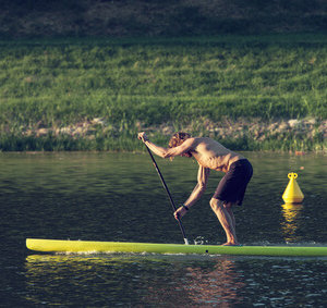 Man paddleboarding at sunset, Florence river, Italy, recreation